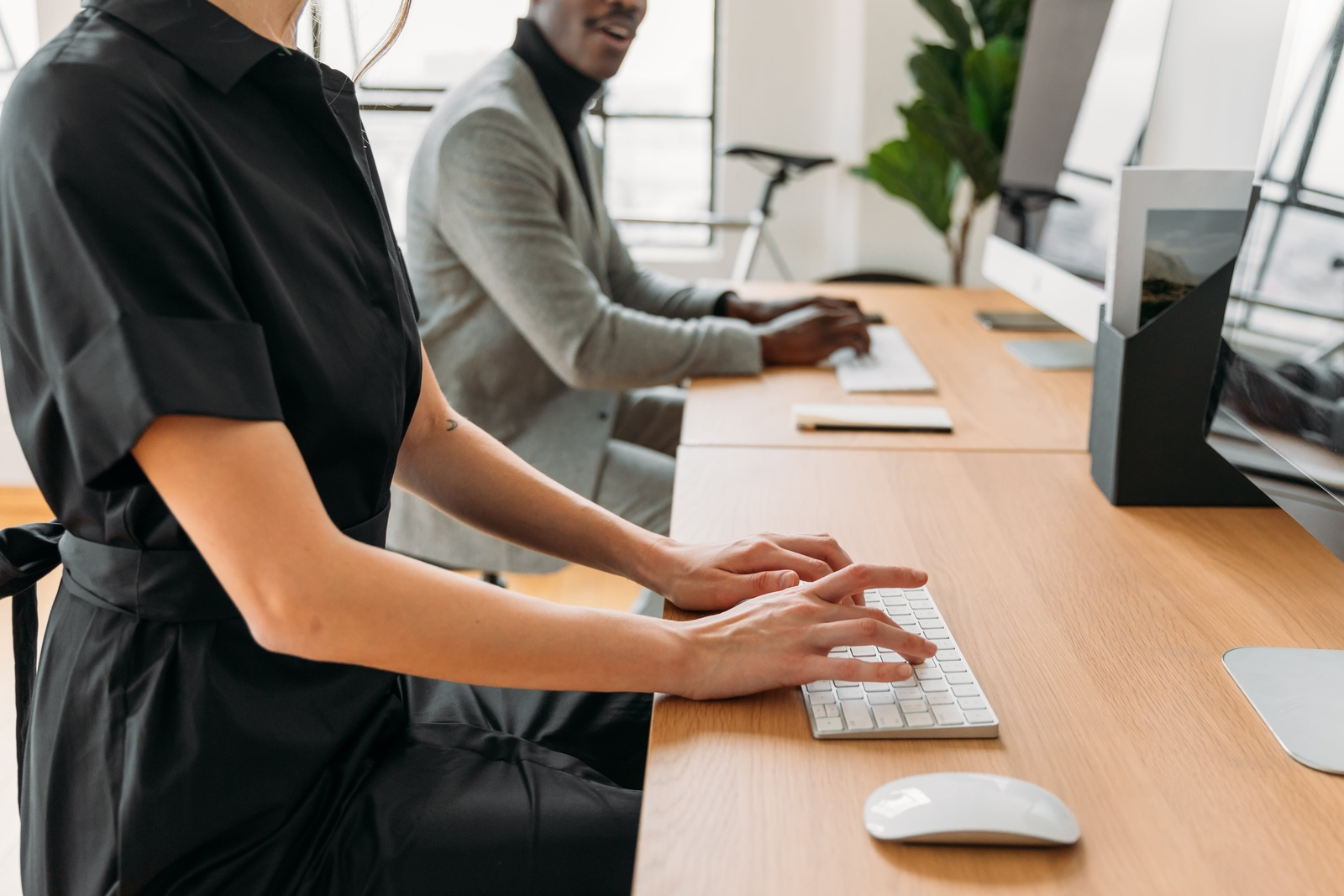 Woman typing at desktop computer