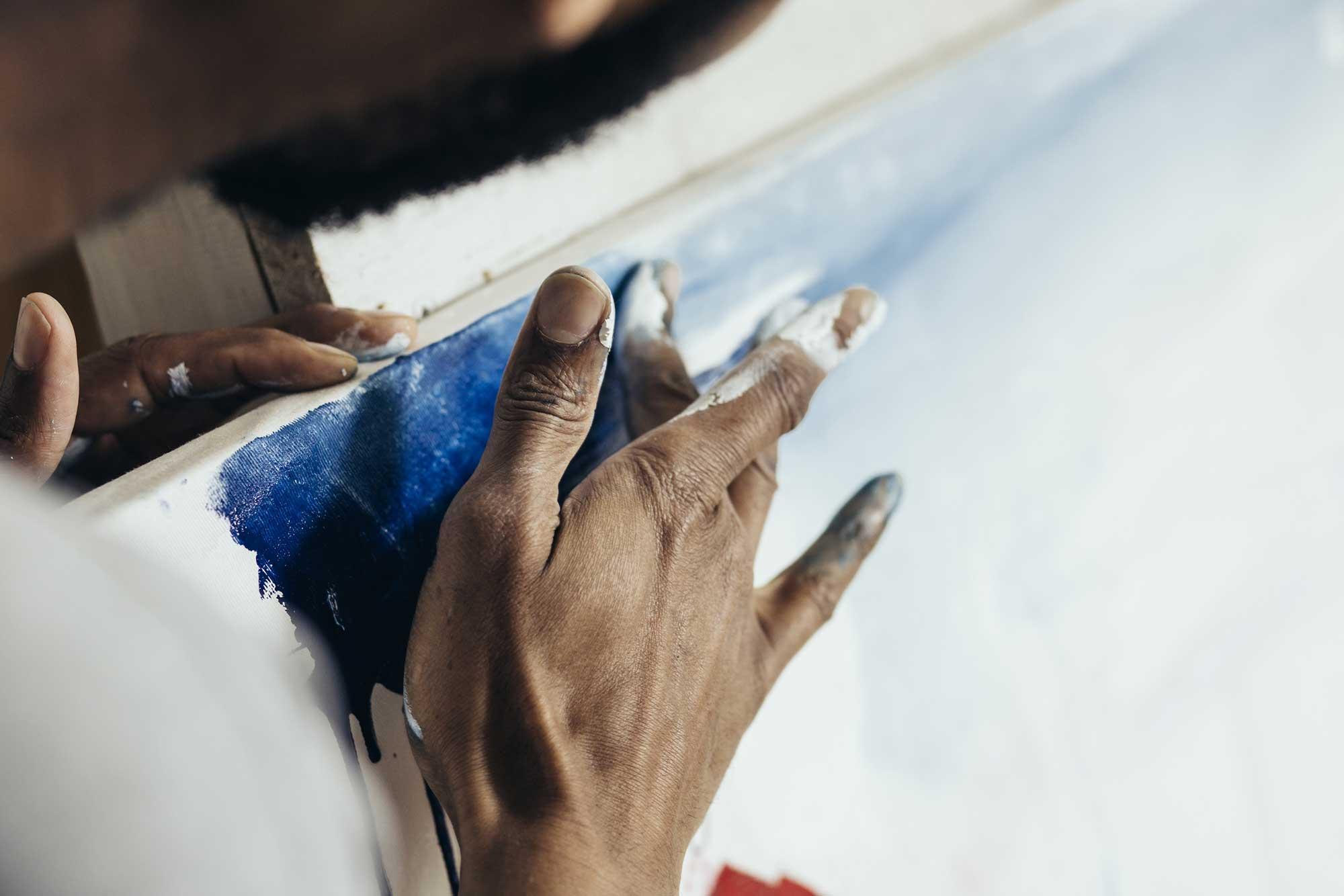 Artist using blue paint
